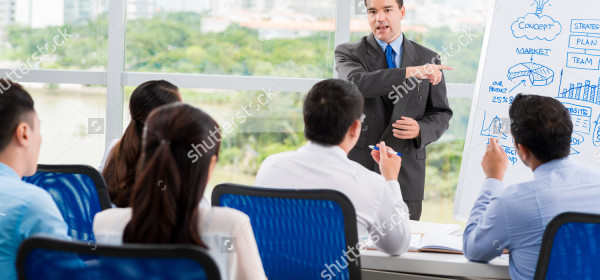 stock-photo-middle-aged-businessman-conducting-seminar-for-his-colleagues-216674437